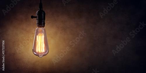 Canvastavla Vintage Hanging Light Bulb Over Dark Wall