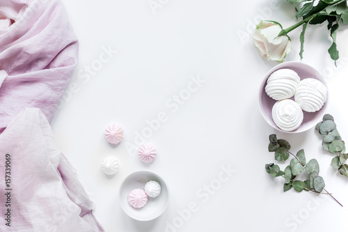 sweet marsh-mallow and flowers on woman white desk background top view mockup