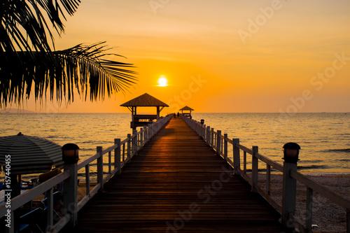 The wooden bridge on sea at sunset, Thailand.