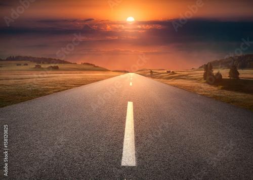 Canvas Print Empty road through mountain scenery at idyllic sunset