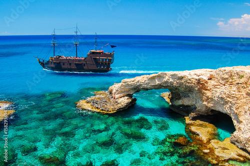 Canvas Print Pirate ship sailing near famous rock arch on Cavo Greko peninsula, Cyprus island