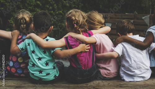 Photo Group of kindergarten kids friends arm around sitting together