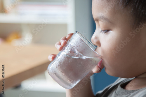 Boy is drinking water in the morning.