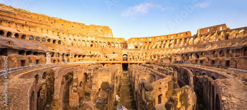 Leinwand Poster Panoramic view of Roman colosseum interior at colorful sunset