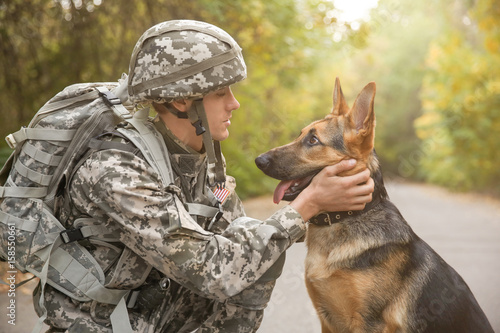 Canvas Print Soldier with military working dog on blurred background
