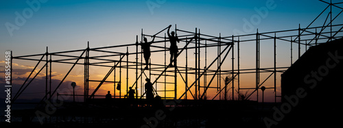 Photo Construction workers working on scaffolding.