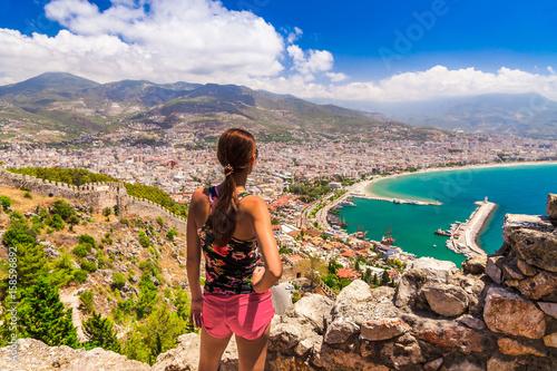 Fototapeta premium Kobieta spojrzeć na krajobraz Alanyi z mariną i czerwoną wieżą Kizil Kule w dzielnicy Antalya, Turcja, Azja. Znana miejscowość turystyczna z wysokimi górami. Letni jasny dzień i brzeg morza