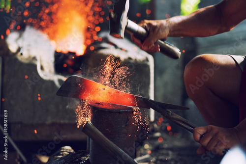 Fotografia Blacksmith handmade fake metal melts on the anvil in the furnace.