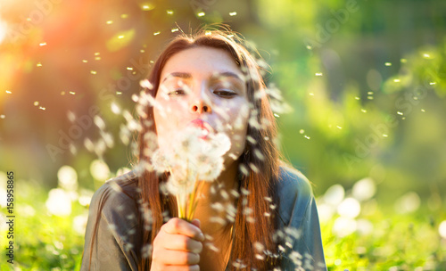 Beautiful young woman lying down on the field in green grass, blowing dandelions and smiling