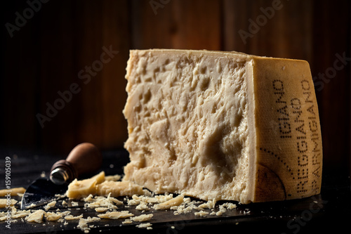 Slice of parmesan cheese with wooden background