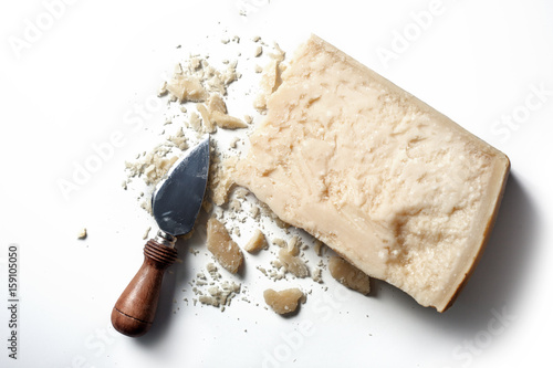 Slice of parmesan cheese with knife over white background