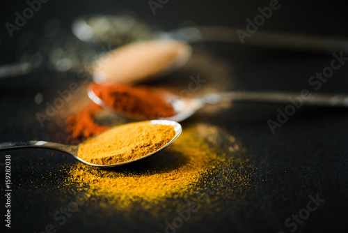 Obraz na plátne close up of various spices and herbs scattered in metal spoon