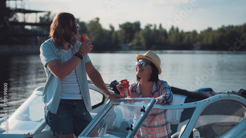 Fotografia Young couple toasting each other with cans of beer as they relax in the evening on a lake in a motorboat while enjoying their summer vacation