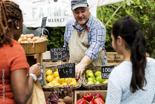 Fotografie, Tablou Greengrocer selling organic fresh agricultural product at farmer market