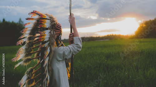 Photo Little girl playing outdoors in the field, wearing Indian headdress, pretending to be a native American