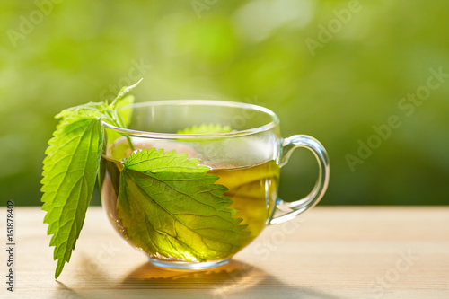 Cup of herbal tea with nettle on wooden background