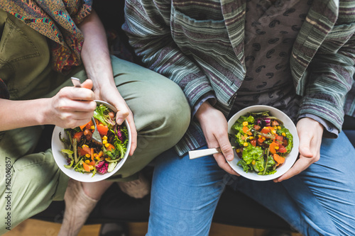Canvas Print Couple eating healty salad at home on the sofa