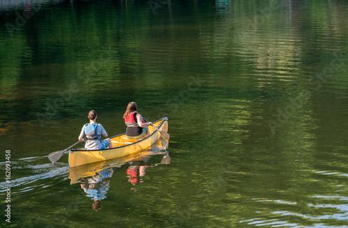 Fotografia Couple paddling in yellow canoe on tree lined lake