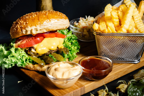 Fotografia Tasty grilled beef burger with fresh vegetables and french fries served hot at l