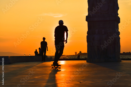 Photo Young man skateboarder skateboarding at sunset, silhouette.