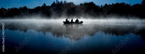 Canvas-taulu silhouette of fisherman on misty blue lake