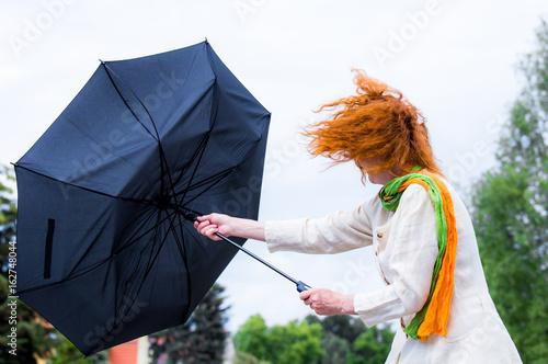Obraz na płótnie eine Frau mit roten Haaren versucht ihren Regenschirm festzuhalten