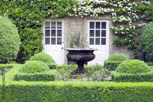 Leinwand Poster Flower vase in green topiary garden in front of a stone English country house, with two patio doors surrounded by white flowering climbing plant