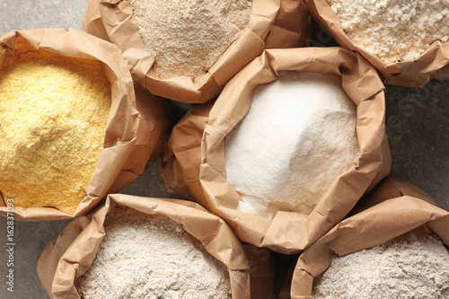 Canvastavla Paper bags with different types of flour on gray background, closeup