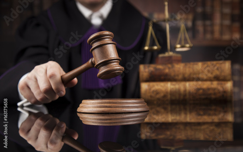 Justice and law concept, Male judge in a courtroom striking the gavel Fototapeta