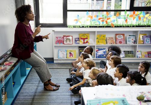 Fotografie, Obraz Kindergarten students sitting on the floor listening to teacher