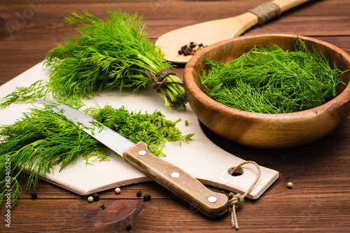 Photo Chopped fresh dill on a cutting board and dill in a wooden bowl on the table