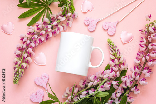 White coffee mug with lupine flowers and hearts on pink background.
