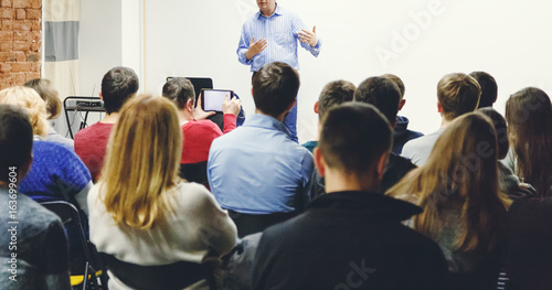 Photo Adult students listen to professor's lecture in small class room