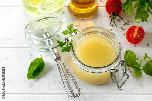 Fotografia Homemade salad dressing vinaigrette with mustard, olive oil, lemon juice and various fresh vegetables and herbs on a wooden background