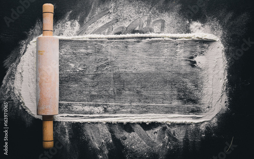 Valokuva Rolling pin and white flour on a dark background