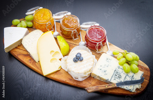 Photo wooden cutting board with cheese and jams