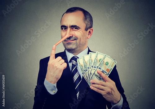 Foto Financial fraud concept. Liar businessman with dollar cash