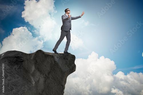 Blindfold businessman standing on tip of cliff Fotobehang