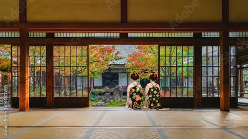 Fototapeta premium Japońska gejsza na Spójrz na ogród japoński kolorową jesienią w świątyni Kenninji w Kioto