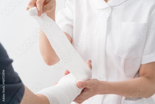 腕に包帯を巻く看護師、患者 Fototapete