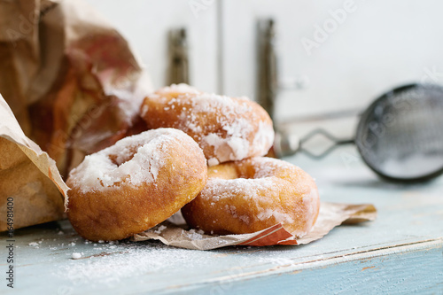 Homemade donuts with sugar powder from paper bag served with vintage sieve on blue wooden table Fototapeta