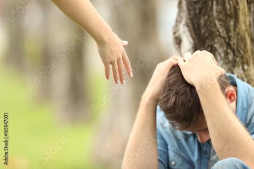 Fotografia Sad teen and a hand offering help
