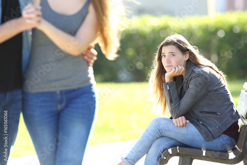 Obraz na plátne Sad girl looking at a couple walking