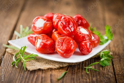 Portion of Red Pepper (stuffed with cheese) on wooden background (selective focus)