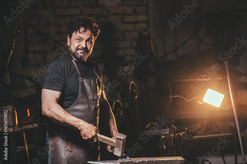 Leinwand Poster Senior blacksmith in smithy.