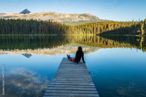 Carta da parati Girl Sitting on dock enjoying the mountains and morring light