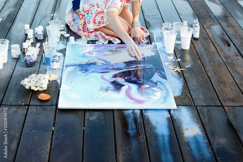 Young beautiful artist woman is painting with acrylic paint on open air session Fototapete