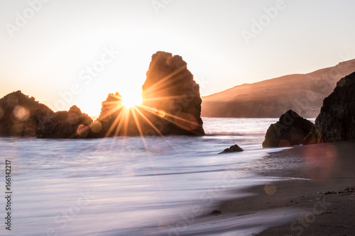 Sunburst between rocks on the beach in the Golden Gate of California