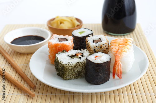 Obraz na plátně Selection of sushi on bamboo mat with chopsticks, soya sauce and pickled ginger