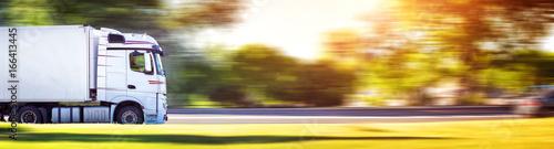 Fototapeta premium asfaltowa droga z plandeką. ciężarówka jadąca w słoneczny wieczór
